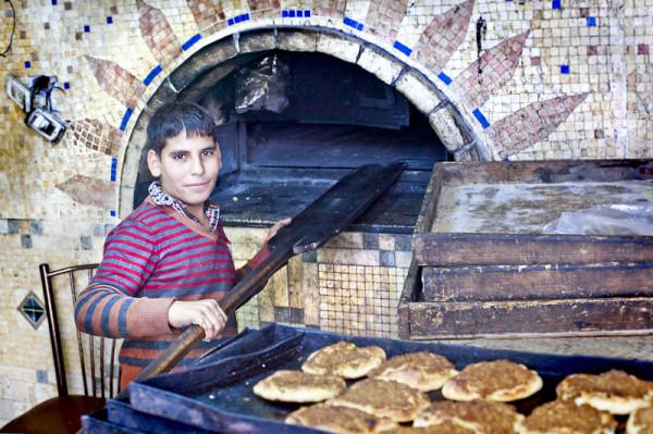 Betlejem. W tym piecu wypiekane są trzy produkty - placki z masą mięsną w pomidorach, kaki - czyli owalne lekko słodkie bułki z sezamem oraz jajka na twardo - tak, jajka na twardo robi się w piecu. Przy piecu pracuję każdy mężczyzna w rodzinie - 13 Mahmud (na zdjęciu), najstarszy, 21 letni Ahmad i najmłodszy, zaledwie ośmioletni Mohamad.