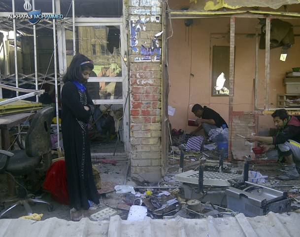 Girl stands at the site of a bomb attack in the Zaafaraniya neighbourhood of Baghdad