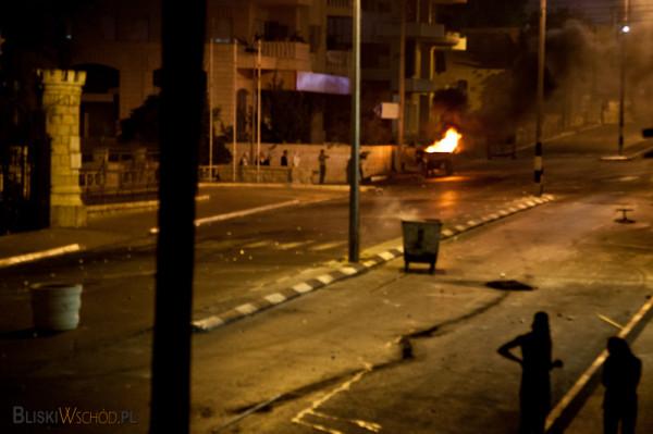 Nieliczna grupa śmiałków - młodych paletyńskich chlopców zbiliża się do muru w Betlejem, gdzie stacjonuje wojsko izraelskie.
