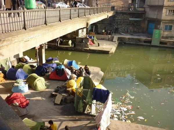 Fot: Goe Swan, Wikimedia, Afghan refugees, living on the Canal Saint Martin in Paris, underneath a bridge 2010